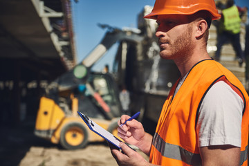 Concentrated professional foreman in orange uniform standing outdoors with blue clipboard in his hands and frowning while making notes