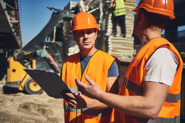 Calm attentive builder in bright uniform looking attentively at his coworker while standing outdoors with him and holding clipboard