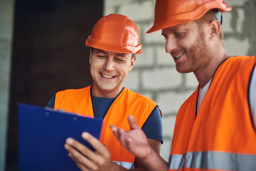 Cheerful friendly builders in bright orange uniform smiling and feeling glad while looking at the notes