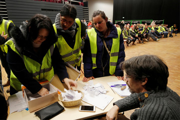 Protesters wearing a yellow vests, the symbol of a French drivers' protest against higher diesel fuel prices, handle ballots as they elect a representative to liaise with other blockade points in Aubevoye