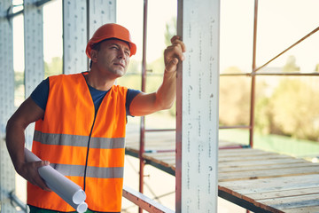 Calm professional builder in orange uniform standing with drawings and thoughtfully looking up while being in incomplete construction