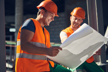 Positive emotional builder in orange vest and helmet smiling happily while sitting with his colleague and looking at the drawing