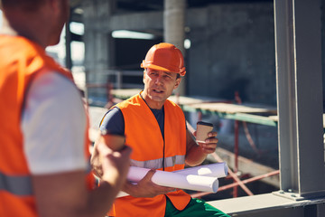 Calm experienced builder wearing orange helmet and vest looking at his coworker while sitting with drawings and a cup of coffee