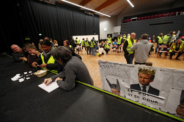 Protesters wearing a yellow vests, the symbol of a French drivers' protest against higher diesel fuel prices, count ballots as they elect a representative to liaise with other blockade points in Aubevoye