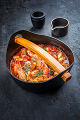 Traditional Asian fish stew with prawns, mussels and fish as top view in a modern design cast-iron roasting dish