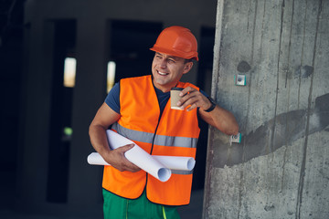 Emotional positive builder wearing orange uniform and smiling while standing with a cup of coffee and looking into the distance