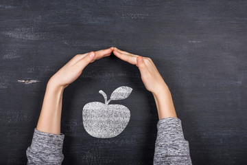 children's hands protect the apple against the background of the blackboard