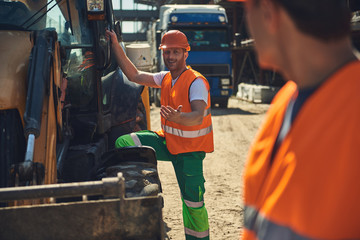 Smiling worker is locating near excavator with his male colleague on construction site