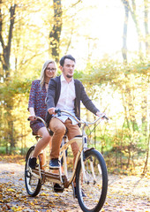 Young couple, bearded man and attractive blond woman in fashionable short dress and glasses riding tandem bicycle along path covered with golden leaves in lit by bright sun beautiful autumn park.