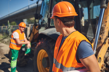 Waist up of two professional workers of construction company are standing near tractor