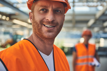 Close up of smiling builder in orange form is standing on hangar with his colleague on background