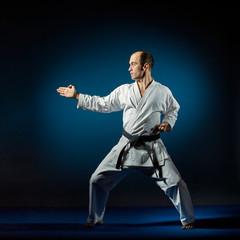 Black belt athlete trains formal karate exercises on blue tatami