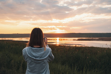 Young woman taking sunrise photos with a smartphone