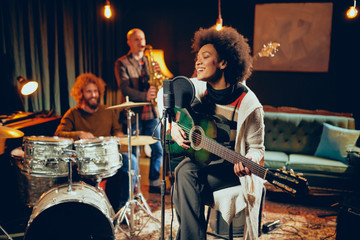Mixed race woman singing and playing guitar while sitting on chair with legs crossed. In background drummer, saxophonist and bass guitarist. Fotobehang