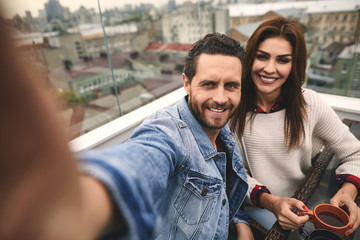 Happy man is making selfie with his cute woman while spending time together