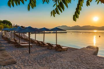 Wall Mural - Nikiana beach with chairs and umbrellas at sunset time, Lefkada island, Greece