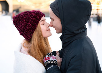 close up young sensual couple holding hands touching noses enjoying romantic moment together outdoors in winter, tender boyfriend and girlfriend standing eyes closed feeling intimacy and closeness