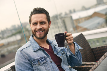 Waist up of adult smiling male with beard is spending time on cozy cafe and drinking coffee