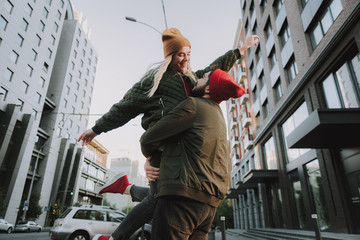 Love and freedom. Portrait of happy beautiful girl in hat raising hand and laughing while boyfriend lifting her up