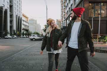 Portrait of handsome bearded man in hat and his charming girlfriend spending time together outdoors. They looking at each other and smiling