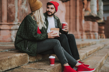 Side view portrait of beautiful girl in hat holding gift box while spending time with boyfriend. Bearded man with cup of coffee looking at her and smiling
