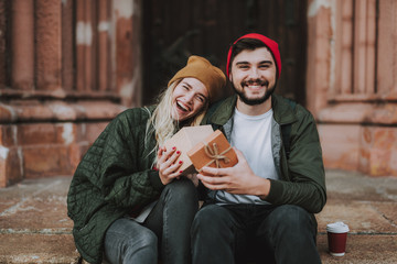 Portrait of beautiful cheerful girl with present having date with boyfriend. They looking at camera and smiling