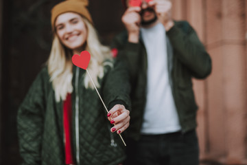 Symbol of love. Close up charming girl in hat holding lovely small heart on stick. Couple on blurred background