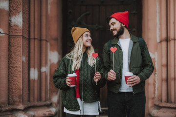 Waist up portrait of charming girl and handsome bearded man in hat holding signs of love and cups of coffee. They looking at each other and smiling