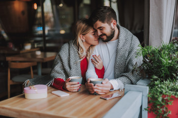Waist up portrait of charming girl with closed eyes holding hand of her boyfriend while snuggling up to him. They sitting at the table and holding cups of coffee