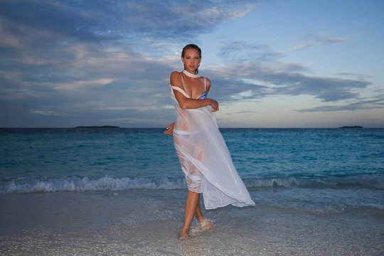 Young woman posing in wet white cloth on the beach at dusk, Fuvahmulah Island, Indian Ocean, Maldives, Asia