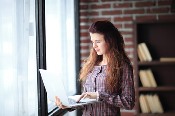 modern business woman is using laptop standing in office.