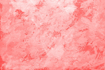 Living Coral color of the Year 2019 on abstract background or decorative texture of old stucco wall, plaster. Home decor.