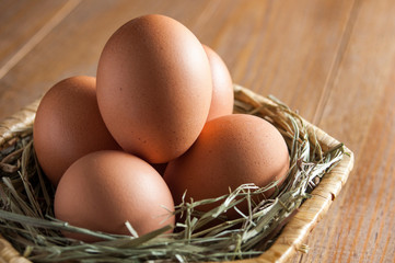 Five large brown eggs lie on a straw bedding in a wicker basket on a wooden table. Still life close-up.
