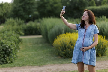 Young pregnant woman taking a selfie in the park