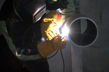 Welder uses torch to make sparks during manufacture of metal cylinder.