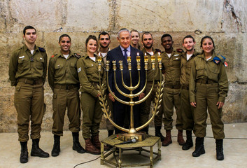 Israeli Prime Minister Benjamin Netanyahu poses for a photo with Israeli soldiers during a candle lightning ceremony on the Jewish holiday of Hanukkah at the Western Wall in Jerusalem's Old City
