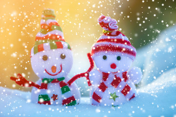 Two small funny toys baby snowman in knitted hats and scarves in deep snow outdoors on bright blue and white copy space background. Happy New Year and Merry Christmas greeting card.