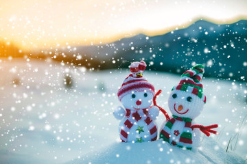Two small funny toys baby snowman in knitted hats and scarves in deep snow outdoors on blurred mountains landscape background. Happy New Year and Merry Christmas greeting card theme.