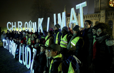 Environmental activists hold letters 'Save the climate, save the people' during the COP24 U.N. Climate Change Conference 2018 in front of the church in Imielin