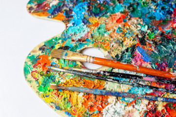 Painting brushes on a colorful palette