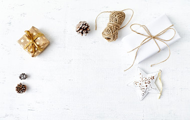 Christmas present, decorations, cones and natural twine on white painted wooden background. Flatlay. Copy space