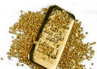 Gold bar in a pile of gold granules. Isolated on a white background.