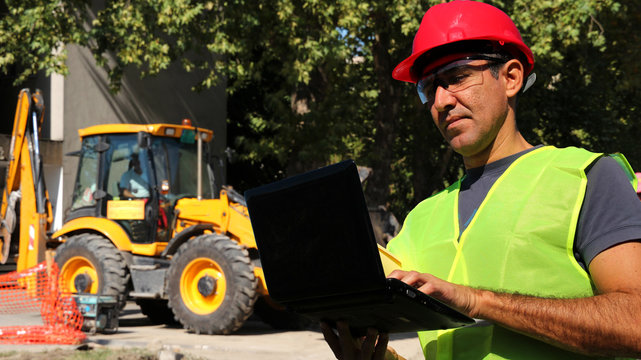 Engineer using laptop in front of wheel loader excavator at construction site