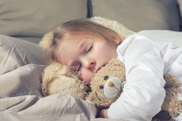 The baby is fast asleep hugging a teddy bear. Little girl with blond hair in bed.