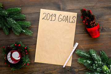 Goals list for New Year 2019 mockup near new year background like spruce branch, candle, festive tree on dark wooden background top view