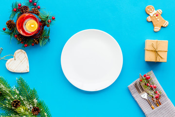 Christmas dinner decoration with gift box, plate and fir tree blue table background top view mock-up