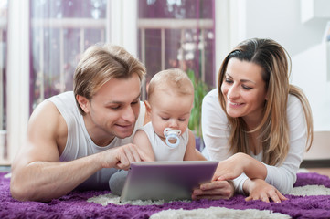 Happy parents laying down on the floor and playing on tablet with their baby boy