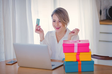 Young girl with holiday gifts and laptop computer holding a credit card. Business, education, shopping and other concept