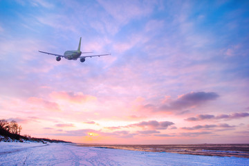 Airplane in the sky over the snowy beach and sea at sunset