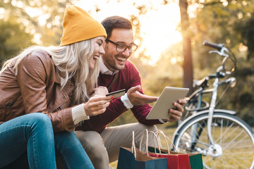 Cheerful young couple shopping online with credit card on a tablet in the park